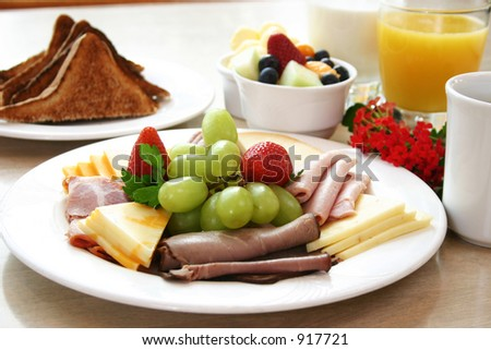 Exotic platter of oven roasted deli beef, ham, sliced turkey & chicken and assorted cheese slices. Topped with fresh strawberries and grapes. Toast, fruit bowl and orange juice complete the meal. - stock photo