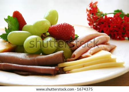 Exotic platter of oven roasted deli beef, sliced turkey & chicken and cheese slices. Served with fresh strawberries and grapes. - stock photo