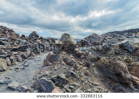 Exotic rocky road to the crater of the volcano. The volcano is located in the famous Caldera of Santorini(Thira) island.Beautiful natural landscape.Cyclades.Greece.Europe. - stock photo