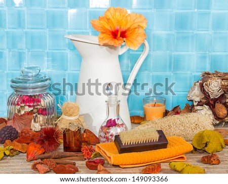 Exotic spa bathing accessories with an orange hibiscus flower in a jug against turquoise blue tiles with rose petal potpourri , bath salts, sponges and a variety of luxury bathing accessories - stock photo