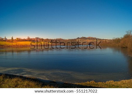 expanse of green grass on the lake with blue sky, countryside and farm around the lake, sunlit water