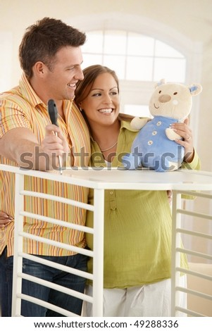 Expectant couple standing together looking at baby toy while putting up baby bed. - stock photo