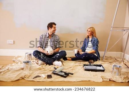 Expectant Couple Taking A Break Whilst Decorating Nursery - stock photo