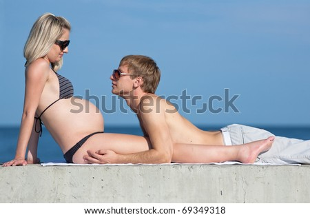 Expectant mother and her husband on the beach. Attractive couple on the beach