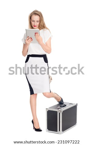 Expectant young woman with a tablet PC and with a suitcase - stock photo