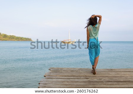 expectation. photo of a woman on the dock that looks into the distance on the outgoing ship - stock photo
