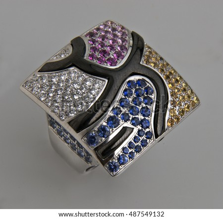 expensive and glamorous ring with stones and gems isolated on a gray background with shadows