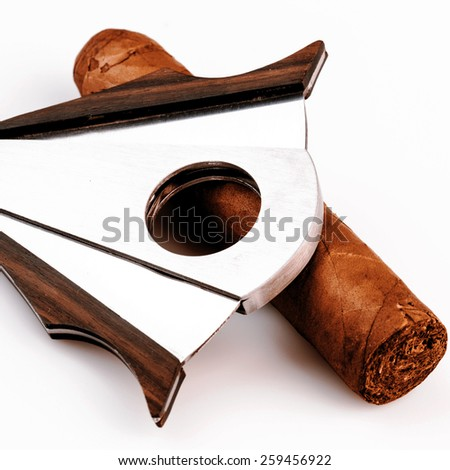 Expensive cigar and cutter on a white background - luxury life style - stock photo