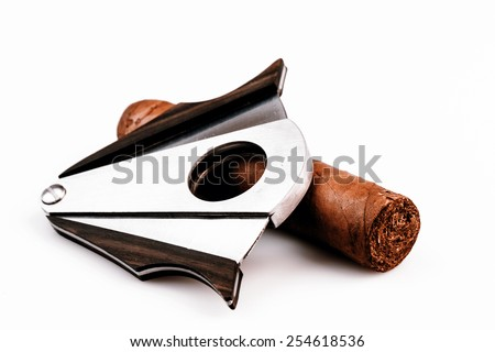 Expensive cigar and cutter on a white background - luxury lifestyle - stock photo