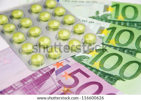 expensive healthcare system with pills and money - stock photo