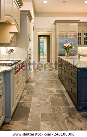 expensive kitchen with slate floors and mixed wood - stock photo