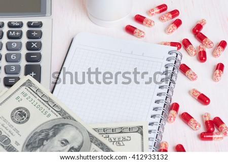 expensive medicine concept. Pills, money and calculator - stock photo