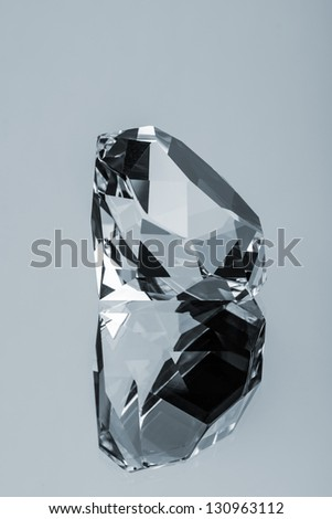 Expensive Translucent Diamond Reflected on Glass Surface - stock photo