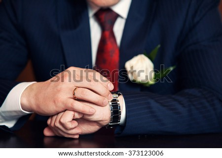 expensive watch at the groom in a suit