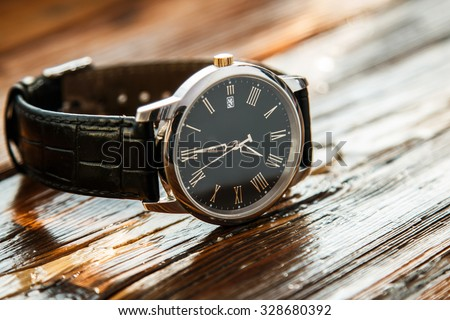 Expensive wrist watch on wooden surface - stock photo