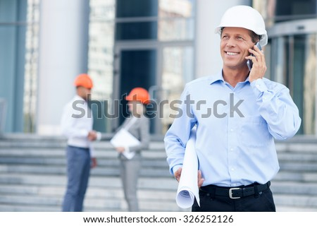 Experienced architect in helmet is talking on mobile phone with customer. He is standing and holding blueprint. The man is smiling. The workers are shaking hands on background - stock photo