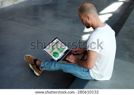 Experienced businessman looking at financial data with graphics and charts while work on a laptop computer, young entrepreneur working with graphs on his notebook,stylish hipster analyzing performance - stock photo