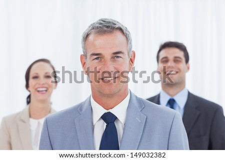 Experienced businessman posing with his work team in bright office