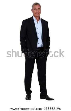 Experienced businessman stood with hands in pockets - stock photo