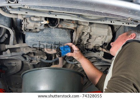 Experienced car mechanic changing oil filter on an engine