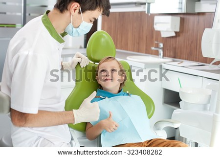Experienced dental doctor is standing near his patient after examining teeth. The boy is looking at man with joy and smiling. He is sitting in dental chair. They are giving thumbs up happily - stock photo