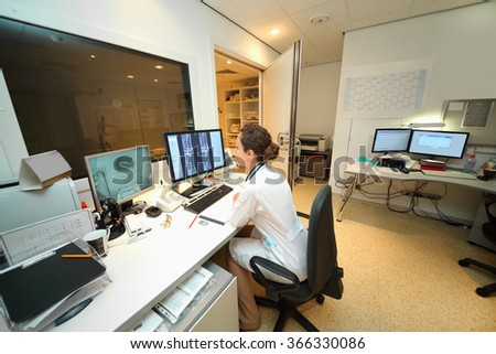 Experienced doctor looking at MRI scan of lumbar region on Monitor in control room - stock photo