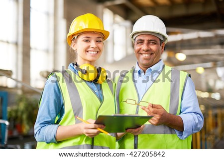 Experienced engineer with his young female trainee - stock photo