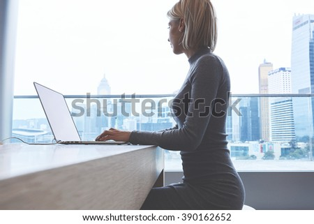 Experienced female freelancer create new design of website on laptop computer while sitting in modern office interior. Young man entrepreneur dreaming about something good while working on  net-book - stock photo