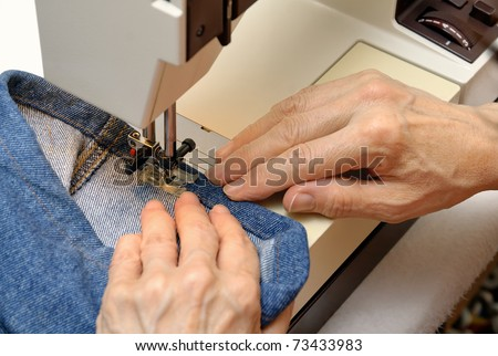 Experienced female hands working on a sewing machine - stock photo