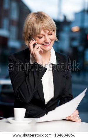 Experienced female manager verifying documents while communicating on phone. - stock photo