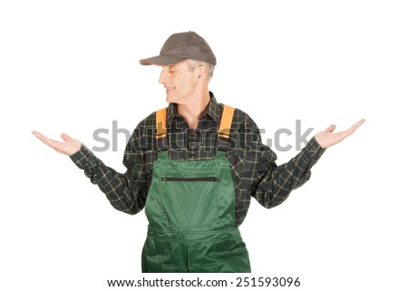 Experienced gardener in uniform showing space in both hands - stock photo