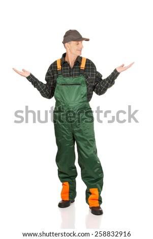 Experienced gardener in uniform showing space in both hands - stock photo