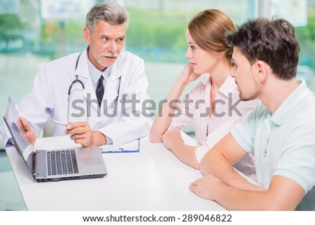 Experienced male doctor explaining to his patients results of analysis with laptop. - stock photo