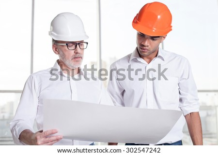 Experienced old architect and handsome young foreman are discussing the project. They are looking at the blueprint seriously. The men are wearing helmets - stock photo