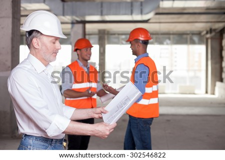 Experienced old architect is looking at sketches with concentration. The young builders are standing behind him. They are talking about building with inspirations and smiling. Copy space in right side - stock photo