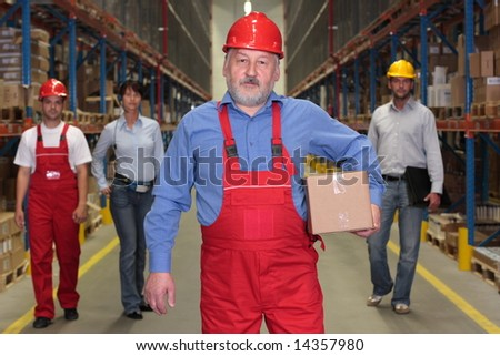 experienced,older worker with parcel at the front of workforce in warehouse - 4 people together - stock photo