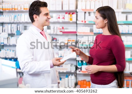 Experienced pharmacist counseling female customer in modern farmacy  - stock photo