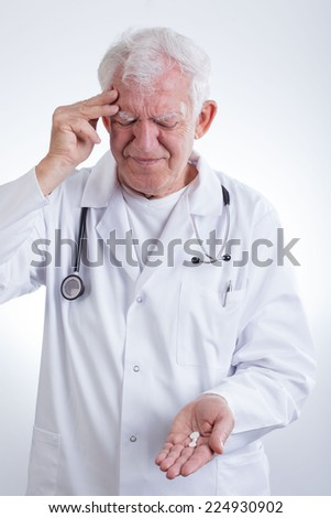 Experienced physician having headache and taking painkillers - stock photo