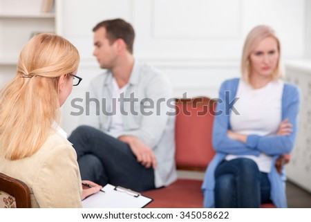 Experienced psychologist is consulting young married couple. She is listening to them attentively and writing. The husband and wife are sitting far from each other with insult - stock photo
