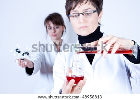 Experienced Scientist Experimenting, her assistant stands behind