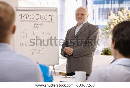 Experienced senior businessman training group about project success in office, smiling.? - stock photo