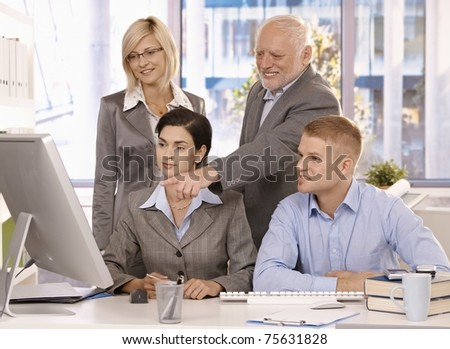 Experienced senior executive working with businessteam, pointing at computer screen, smiling.? - stock photo