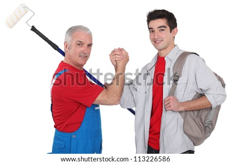 Experienced tradesman making a pact with his new apprentice - stock photo