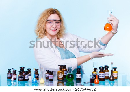 Experiment, research in progress. Chemist woman or student girl, laboratory assistant or scientific researcher with chemical glassware test flask on blue - stock photo