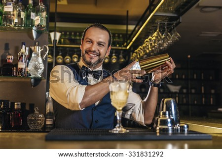 Expert barman is making cocktail at night club - stock photo