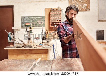 Expert carpenter in his workshop, looking down the length of a wooden plank, checking it for quality and straightness - stock photo