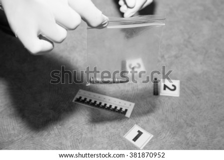 Expert examines a bullet at the crime scene - stock photo