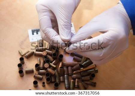 Expert examines a bullet at the crime scene. investigation of th - stock photo