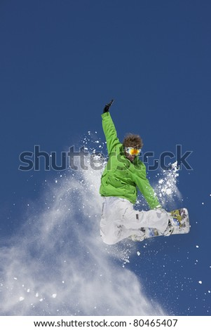 Expert high in air making extreme snowboard jump against blue sky.