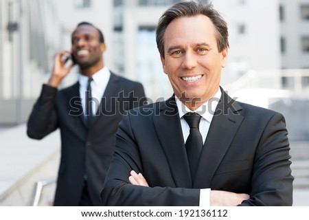 Expert in business world. Confident senior man in formal wear keeping arms crossed and smiling while African man talking on the mobile phone in the background   - stock photo